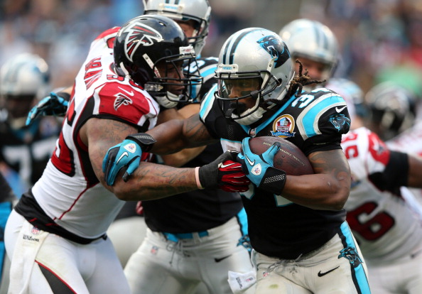 CHARLOTTE, NC - DECEMBER 09: John Abraham #55 of the Atlanta Falcons tries to tackle DeAngelo Williams #34 of the Carolina Panthers during their game at Bank of America Stadium on December 9, 2012 in Charlotte, North Carolina. (Photo by Streeter Lecka/Getty Images)