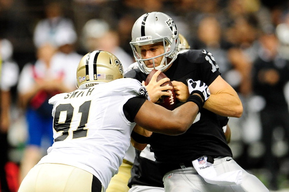 NEW ORLEANS, LA - AUGUST 16:  Matt Flynn #15 of the Oakland Raiders is sacked by Will Smith #91 of the New Orleans Saints during a preseason game at the Mercedes-Benz Superdome on August 16, 2013 in New Orleans, Louisiana.  (Photo by Stacy Revere/Getty Images)