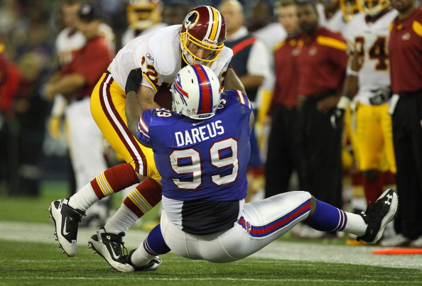 TORONTO, ON - OCTOBER 30: John Beck #12 of the Washington Redskins is sacked during NFL game action by Marcell Dareus #99 of the Buffalo Bills at Rogers Centre on October 30, 2011 in Toronto, Ontario, Canada. (Photo by Tom Szczerbowski/Getty Images)