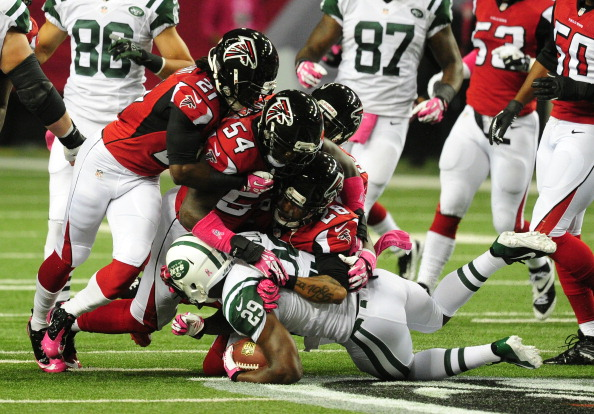 ATLANTA, GA - OCTOBER 7: Bilal Powell #29 of the New York Jets is tackled by Thomas DeCoud #28, Stephen Nicholas #54, and Desmond Trufant #21 of the Atlanta Falcons at the Georgia Dome on October 7, 2013 in Atlanta, Georgia. (Photo by Scott Cunningham/Getty Images)