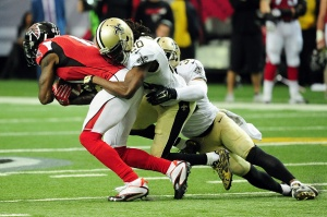 ATLANTA, GA - JANUARY 03:  Julio Jones #11 of the Atlanta Falcons is tackled after a catch by  Brian Dixon #20 of the New Orleans Saints during the second half at the Georgia Dome on January 3, 2016 in Atlanta, Georgia.  (Photo by Scott Cunningham/Getty Images)