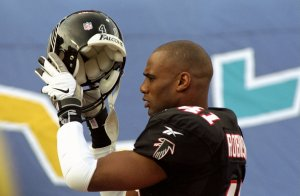 31 Jan 1999: Eugene Robinson #41 of the Atlanta Falcons puts on his helmet during team introductions for Super Bowl XXXIII between the Atlanta Falcons and the Denver Broncos at Pro Player Stadium in Miami, Florida. Robinson was arrested for alleged solicitation the night before but was released to play the game.
