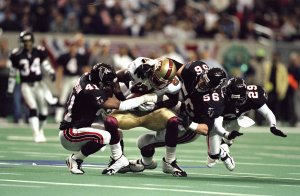 The Falcons defense led by Keith Brooking and Eugene Robinson swarms over Terrell Owens of the 49ers during the NFC Divisional Playoff game at the Georgia Dome in 1999. (Getty Images)